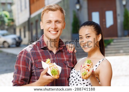 Going to eat. Young Caucasian man and Asian woman standing on street and holding hotdogs - stock photo