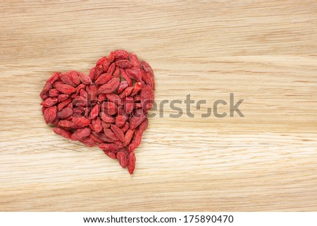 goji berries in heart shape on wooden surface - stock photo