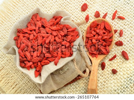 Goji berries in the sacking on a wooden background. Vitamin c fruit. - stock photo