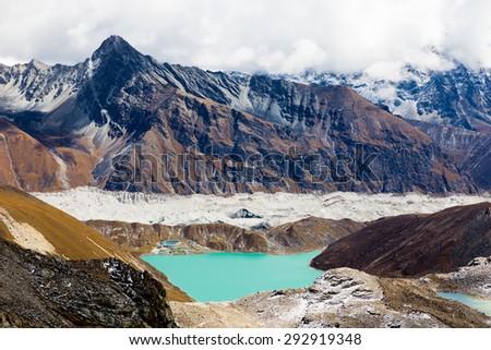 Gokyo lake village lodges , Ngozumpa glacier snow mountains peaks ridge panorama view from Renjo La pass. Everest Base Camp trail route, Nepal traveling trekking, Himalaya tourism landscapes. - stock photo