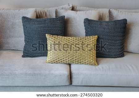 gold and black color pillows on grey sofa in living room - stock photo