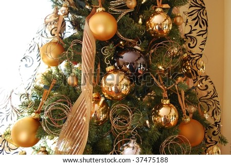 Gold and black ornaments on a christmas tree.
