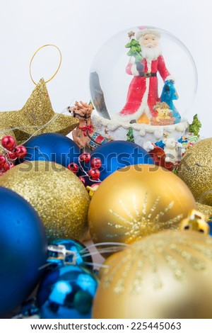 Gold and blue Christmas decorations  and Santa Claus in a glass bowl