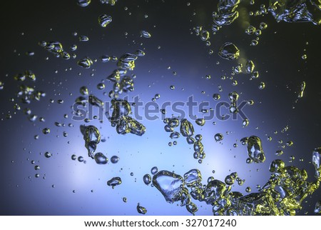 gold and colored bubbles in dark water