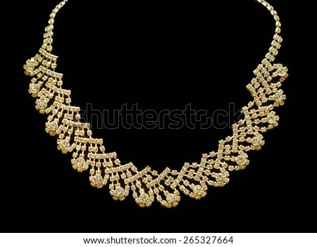 Gold and diamond necklaces isolated on black background - stock photo