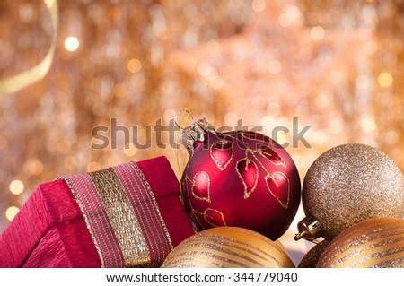 gold and red christmas baubles and red box on background of defocused golden lights.