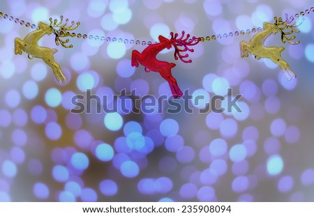 gold and red christmas reindeer isolated on Lights blue background. - stock photo