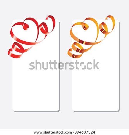 Gold and red curling ribbons in shape of heart over the greeting cards. Vertical orientation  - stock photo