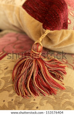 Gold and red tassel hanging from the corner of a velvet cushion - stock photo
