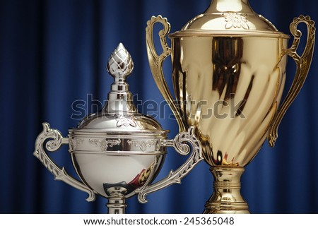 Gold and silver cups on a background of dark blue cloth - stock photo