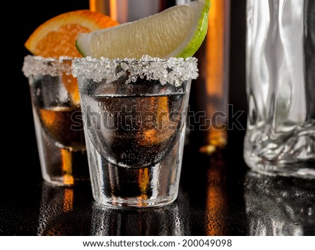 Gold and silver tequila with lime or lemon and orange - stock photo