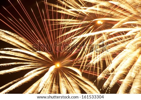 Gold and yellow fireworks exploding in the night sky. - stock photo