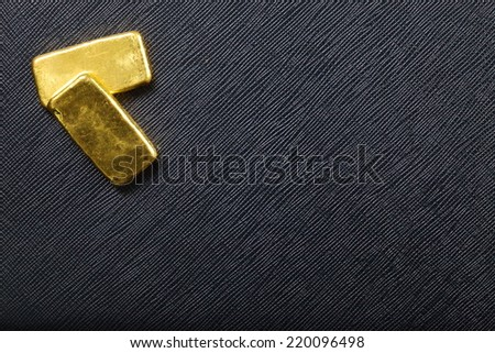 Gold bar put on on the black color artificial leather surface background show the whole bar. - stock photo