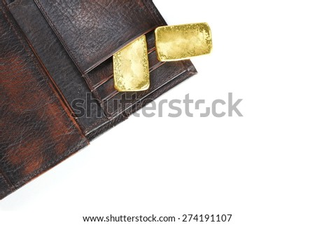 Gold bar put on the brown color leather wallet represent the business and investment concept idea.