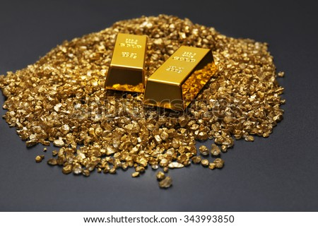 Gold bars and nugget grains, on grey background - stock photo