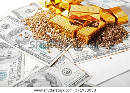 Gold bars and nuggets on dollar banknotes, close up - stock photo