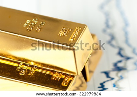 Gold bars on graphs and statistics. - stock photo