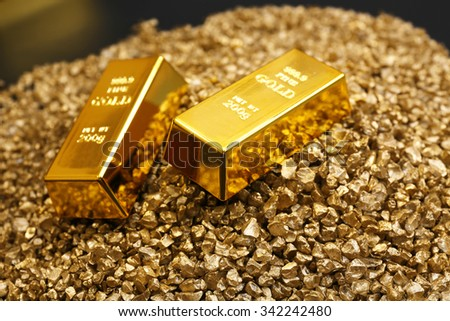 Gold bars on nugget grains background, close-up - stock photo