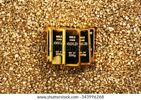 Gold bars on nugget grains background, close-up, top view - stock photo