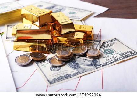 Gold bars with dollar banknotes and euro coins on paper background - stock photo