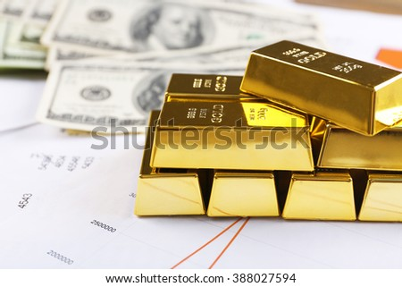 Gold bars with dollar banknotes on paper background - stock photo