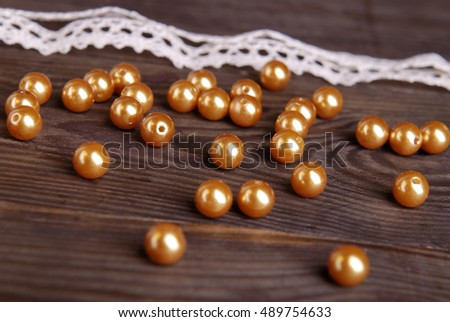 Gold beads and white lace on a dark wooden background.