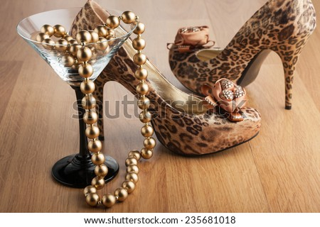 Gold beads in a martini glass on the background of  leopard shoes - stock photo