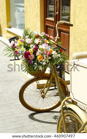 Gold bicycle with basket of colorful flowers outdoors