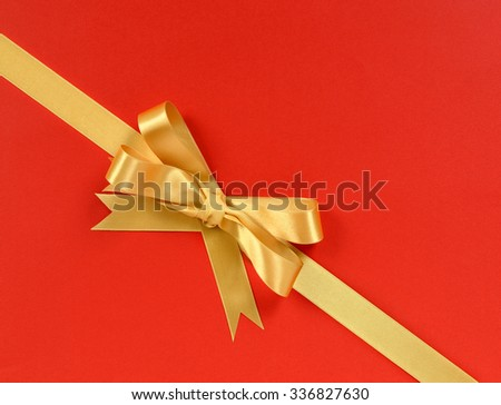 Gold bow gift ribbon corner diagonal isolated on red paper background