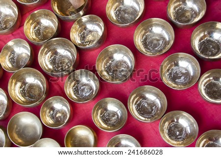 Gold bowls wtih water on a pink cloth. - stock photo