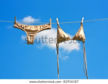 gold bra and panty hanging on clothesline - stock photo