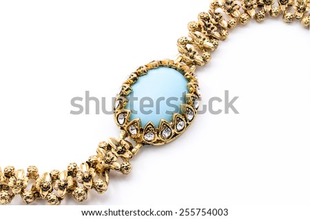 gold bracelet with blue stone on a white background