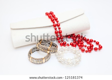 Gold bracelets red and white necklace with purse on white background - stock photo