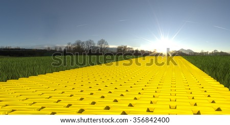 Gold brick road on grass with sun and blue sky - stock photo