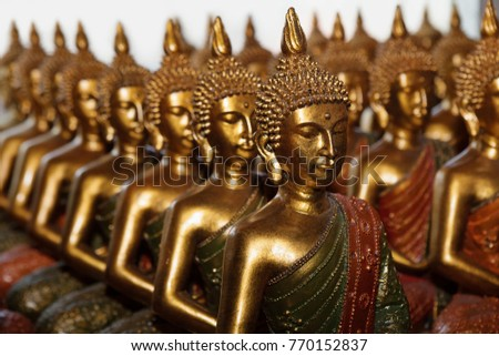 Gold Buddha statues sitting in row on white background. Statues in Buddhist Thailand temple or wat, are public domain or treasure of Buddhism, no restrict in copy or use.