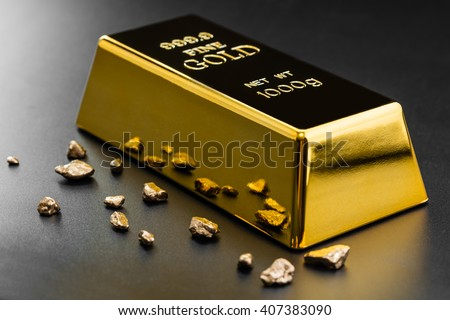 gold bullion and nuggets on a dark background