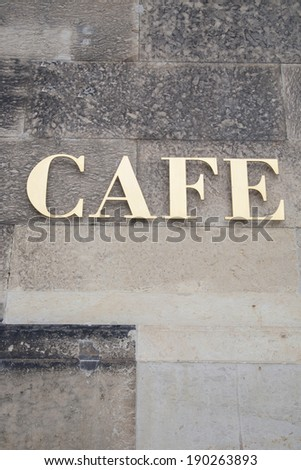 Gold Cafe Sign on Stone Wall