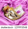 gold carnival masks on magenta silk fabric - stock photo