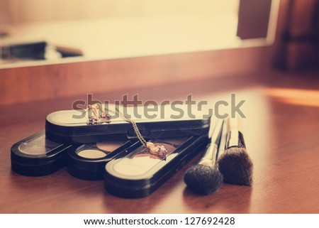 Gold chain lying on Palette of eye shadows and brushes on the table - stock photo