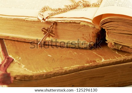 Gold chain with a cross on a background of old battered books - stock photo