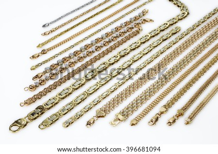 Gold chains and bracelets are parallel to the smoky white plastic