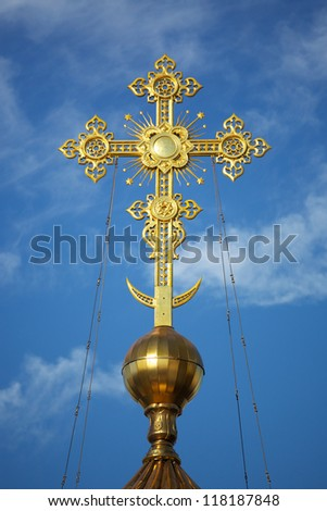 Gold Christian cross on a background of blue sky - stock photo