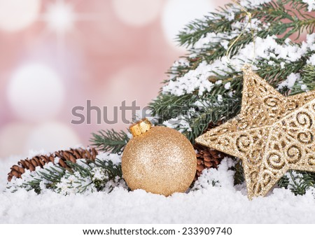 Gold Christmas ball and star with evergreen tree branch in snow