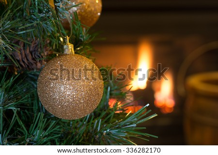 Gold Christmas ball hanging on a tree with fireplace in background - stock photo