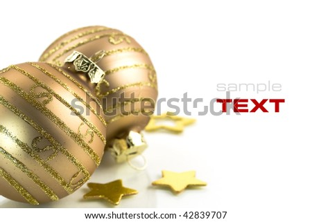 Gold Christmas balls and stars on white background (with sample text) - stock photo