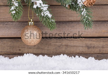 Gold Christmas bauble hanging from evergreen branch with a wood background