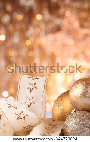 gold christmas baubles on background of defocused golden lights.