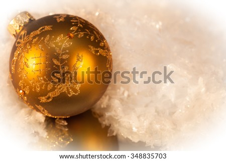 Gold christmas ornament ball on a soft white background with small reflection