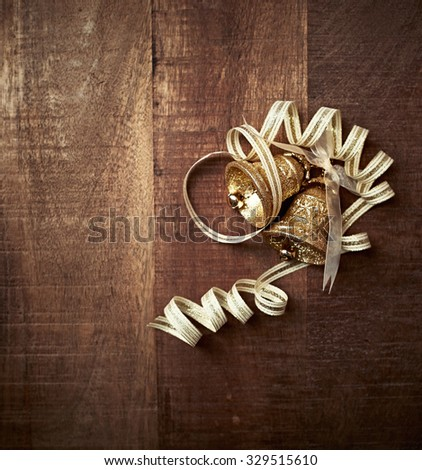 Gold Christmas ornaments on a rustic wooden background - stock photo