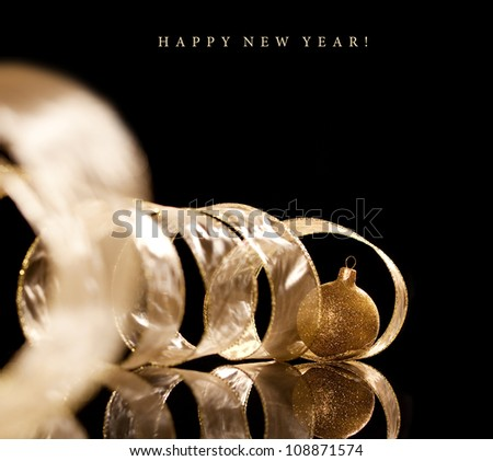 Gold christmas sphere with ribbon on black background. Christmas decoration - stock photo